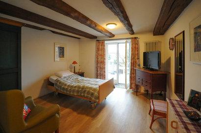 Ein typisches Bewohnerzimmer, hier mit Balkon zum Garten hin.