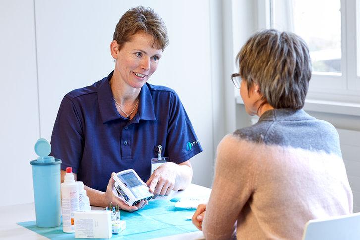 Pflegefachfrau von SPITEX BASEL unterstützt eine Dame mit Informationen zu einem Messgerät.
