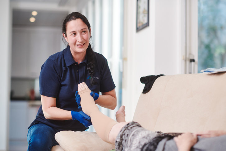 Pflegefachfrau zieht einer Kundin Kompressionsstrümpfe an