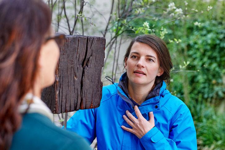 Spezialisierte Pflegefachperson im intensiven Gespräch mit einer jungen Frau draussen