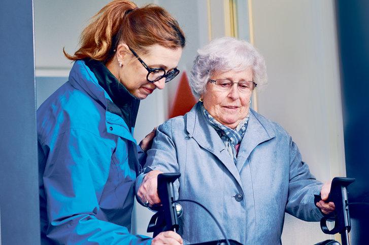 Mitarbeiterin von SPITEX BASEL hilft betagter Frau mit Rollator aus dem Haus