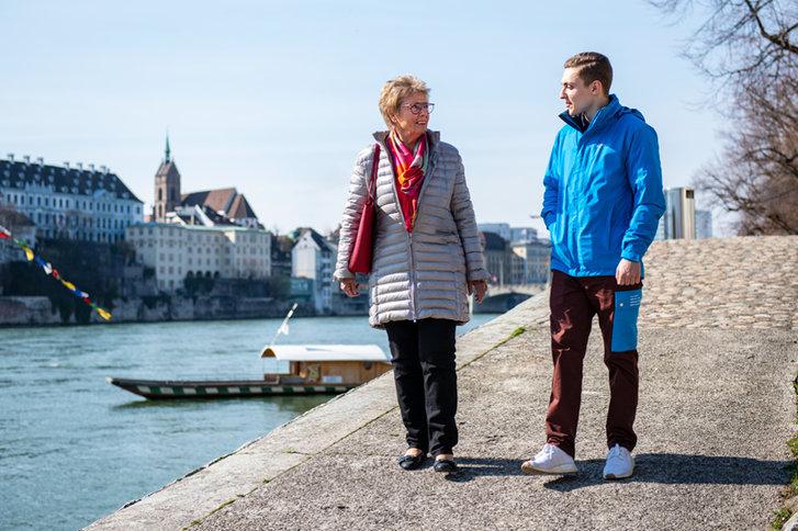 Zivildienstleistender spaziert mit älterer Dame am Rhein